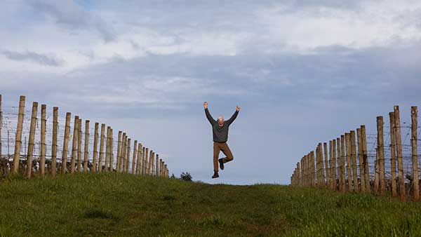Tyson Crowley jumping for joy in the vineyard.